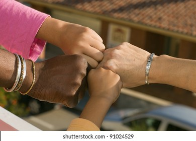 four fists of different ages and different race, photo taken outdoors