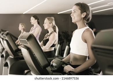 Four fit women running on treadmills in modern gym