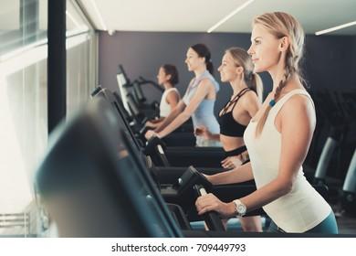 Four fit women running on treadmills in modern fitness center