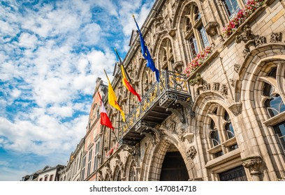Four flags in city center of Mons, Belgium. European flag, Belgian flag, Walloon flag, Flag of Mons.