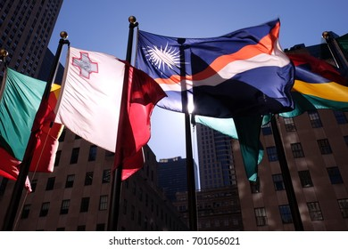 four flags floating in the wind with skyscraper in the background. Sun reflecting through the flags in NYC (USA)