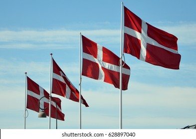 Four flags flying in the wind against blue sky - Denmark red and white