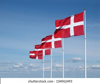 four flapping danish flags on clear blue sky
