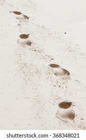 Four footprints of a human on the beach sand, leading diagonally towards the viewer