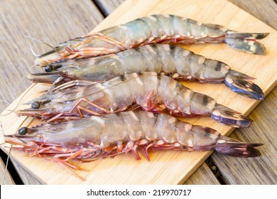 Four fresh whole tiger prawns laid out neatly on a wooden board to be used as an ingredient in gourmet seafood cuisine