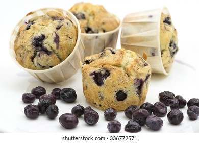 Four freshly baked blueberry muffins and some fresh berries fruit on the foreground.  Two of the background muffins are blur. White background.