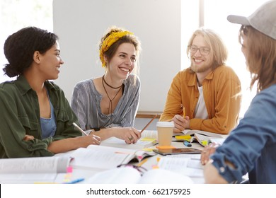Four friendly mixed race students sitting in white classroom reading books and communicating together talking about their summer holidays being absorbed in studying having smiles on their faces