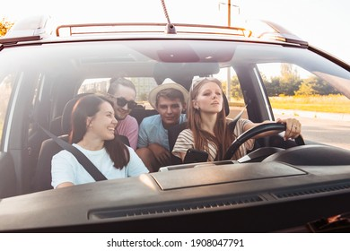 four friends in car navigation on phone. road trip