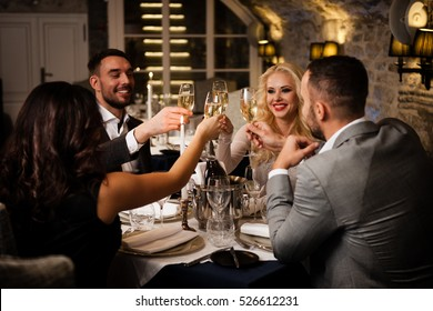Four friends with champange glasses celebrating and toasting in restaurant