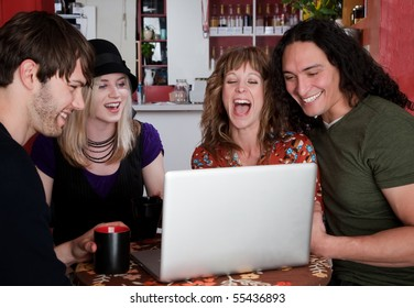 Four friends in a coffee house with laptop computer