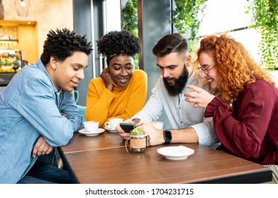 Four friends discussing a topic while looking at the phone in the cafe.