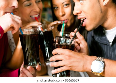 Four friends drinking soda in a bar with colorful straws