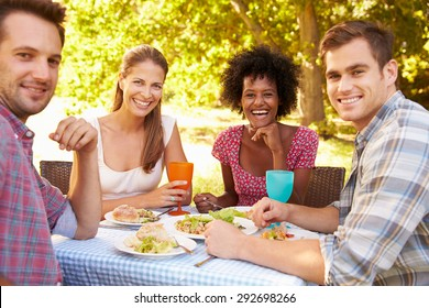 Four friends eating together outdoors