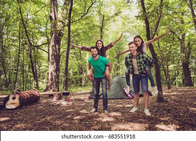 Four friends are fooling around in a wood at a campground, boys piggyback their ladies