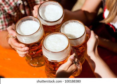 Four friends with a fresh beer in a Beer garden, close-up on beer stein