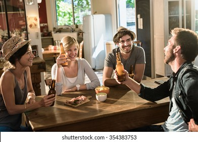 Four friends having a drink after work. They are sitting at a wooden table lifting their bottles of beer in a cozy house. They are smiling and looking at each other, wearing casual clothes and hats.