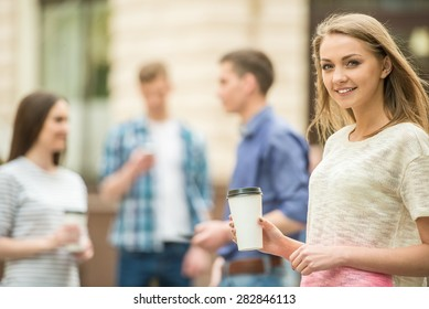 Four friends having fun outdoors and drinking coffee. Double couple date.