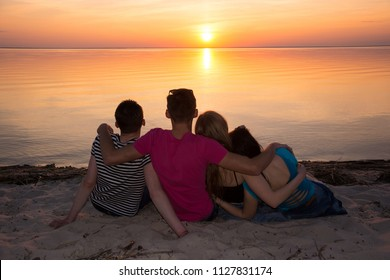 Four friends hugging on the beach and admiring the sunset. Young people - guys and girls - sit on the beach and watch the sunset. Guys and girls, students are embrace in front of a sea at sunset