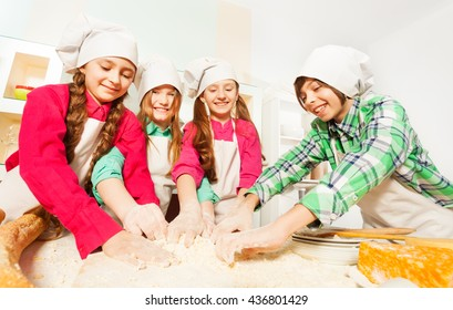 Four friends kneading bakery dough at the kitchen
