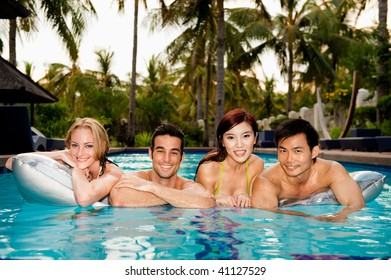 Four friends lying on an airbed in the swimming pool
