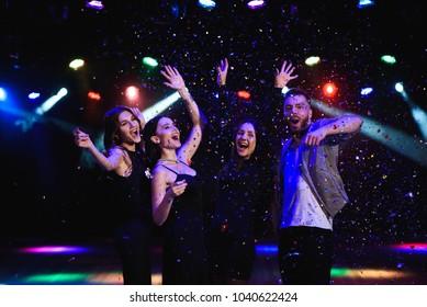 Four friends making having fun among confetti