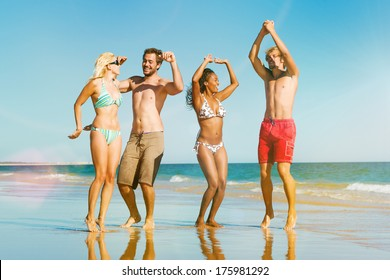 Four friends - men and women - on the ocean beach having lots of fun in their vacation jumping in the water