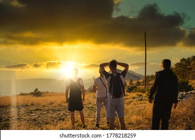 Four friends seen from behind, hiking on top of the Mosor mountain in Croatia. Strong colorful sun setting seen going behind the hill while people watch in awe
