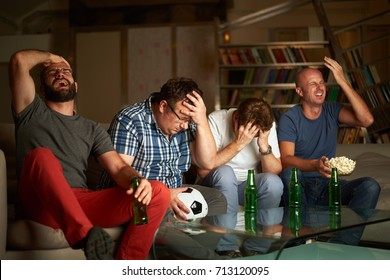 Four friends sitting on sofa and showing frustration while watching football game