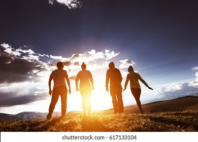 Four friends stands in sunset light on background of blue sky in mountain range. Space for text