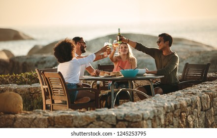Four friends toasting drinks sitting on a dining table outdoors near the seashore. Multiethnic friends on a holiday having fun drinking wine and snacks.