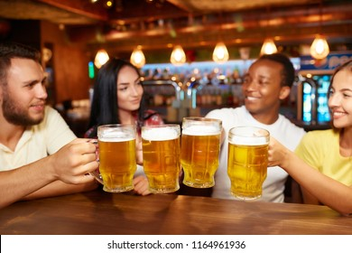 Four friends toasting with glasses of light beer at pub. Group of people drinking beer, having fun together, raising beer clinking glasses above table with snacks. Friendship and party concept.
