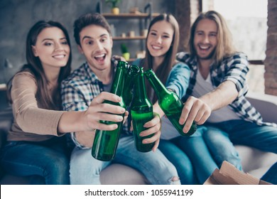 Four friends, two couples having small home party, meeting, sitting on couch, clinking bottles of beer, spending, enjoying  time together, watching tv