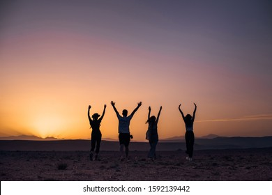 four friends walk through the sugar desert in the heat of the sun. silhouette. they raised their hands up the mountain and enjoyed. Walking friends in desert in Morocco at sunset