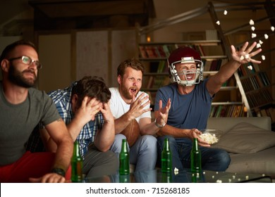 Four friends watching american football game, showing frustration