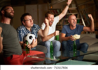 Four friends watching football game on TV, sitting on sofa