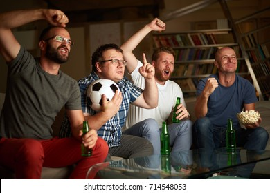 Four friends watching football game in front of the tv