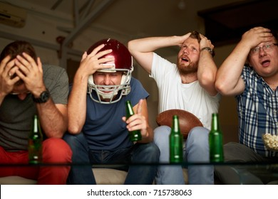 Four friends watching game of american football, feeling frustrated and disappointed