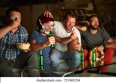 Four friends watching game of american football in front of TV