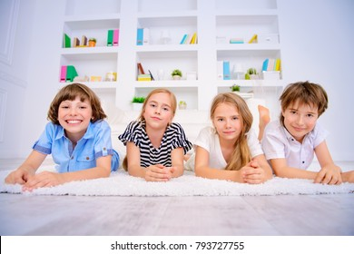 Four funny children lie on the floor at home and laugh. Child concept.