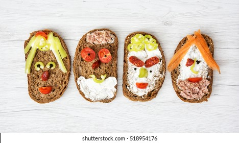 Four funny faces made of bread, butter, tuna, sausage, carrot, paprika, tomato and black pepper. Humorous creative food. Facial expression.
