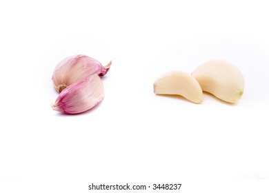 four garlic cloves, two peeled, two unpeeled, isolated on white