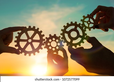 four gears in hands on a sunset background. teamwork.