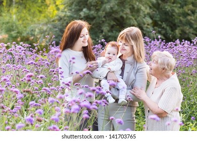 Four generations of beautiful women standing in a lavender field