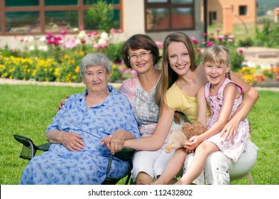Four generations of women sitting together at countryside and smiling