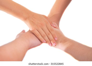 Four girl friends holding hands in a pile of unity - isolated on white - showing teamwork and friendship