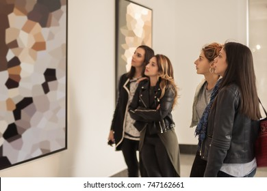 Four girl friends looking at modern painting in art gallery. Abstract painting