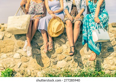 Four girlfriends sitting on a wall outdoors with spring and summer dresswear - Women meeting and having fun in a countryside - Concepts about friendship,seasonal,lifestyle and shopping