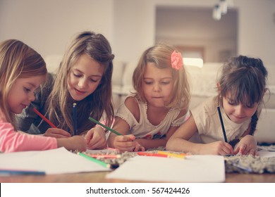 Four girls lying on the floor and write their homework.