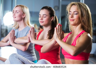Four girls meditating after fitness training in gym.Group of young women in the gym centre. Yoga.