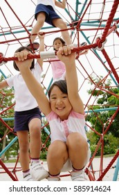 Four girls at playground, climbing on jungle gym